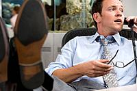 Businessman with feet up at desk, on telephone