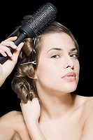 Woman styling her hair (thumbnail)