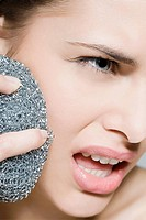 Woman using scouring pad on her face