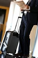 Businessman waiting with luggage and reading newspaper