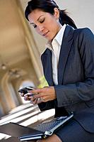 Businesswoman checking text messages outdoors
