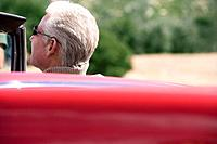 Senior man sitting in red convertible