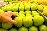 Woman selecting green apple