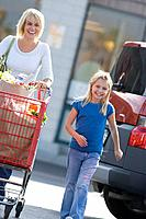 Mother with daughter pushing grocery cart full of groceries