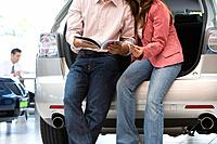 Couple reading brochure in car showroom