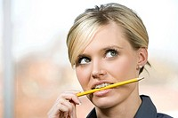 An office worker biting on a pencil