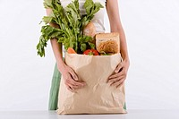 Young woman holding paper bag filled with groceries
