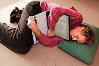 Middleaged man is lying on the floor with a notebook