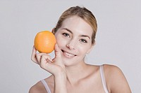 Young woman holding orange, portrait