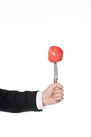 Businessperson holding knife with apple, close_up
