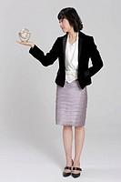 Businesswoman holding globe on palm, close_up
