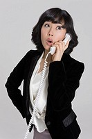 Business woman using landline phone, looking up