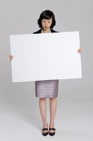 Businesswoman holding cardboard, close_up