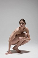 Naked Young woman crouching, portrait