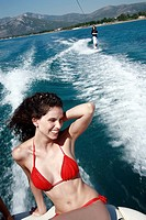 Female young adult on speedboat,male waterskiing