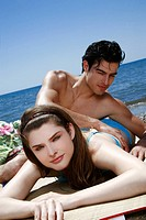 Young adult couple on beach sunbathing