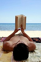 Young male adult reading book on beach