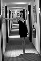 attractive brown-haired woman in black underwear in a hotel corridor