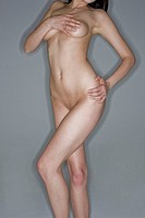 Naked woman covering breast with hand, close_up