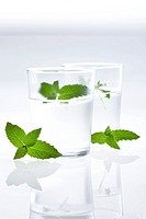 Mint leaves with glass of water in background, close_up