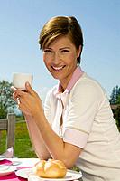 portrait of smiling woman sitting at breakfast table outdoors