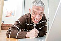 portrait of happy mature man working with laptop computer at home