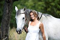 young woman with white horse in summer