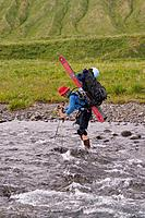 A woman skier crossing a river on Umnak Island in the Aleutian Islands