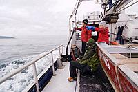 Friends on a fishing boat on a cloudy day in the Aleutian Islands
