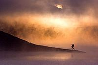 A man hiking along the shore of a misty lake at dawn near Truckee California