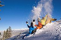 Four friends sitting in the snow throwing snow into the air at Northstar ski resort near Lake Tahoe California