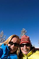 Two girlfriends smiling on the deck of a ski lodge on a sunny day at Northstar ski resort