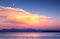 The full moon and a thunderhead cloud over Lake Tahoe California at sunset