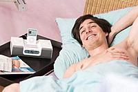 Man, young, bed, lying, smiling, alarm clock, Apple iPod video, no property release, series, people, men´s_portrait, wakes up, enjoying, cheerfully, m...