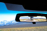 View from inside of a car with rearview mirror displaying highway, mountains, and trailing semi-truck