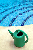 Watering can by swimming pool