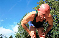Man, 40-45, partially bald, bending over to rest after running