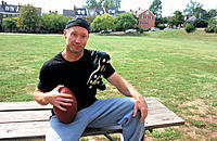Man, 40-45, sitting on park bench, holding football