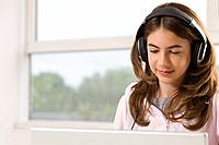 Girl with earphones and computer