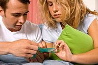 Teenage boy and girl holding condom (thumbnail)