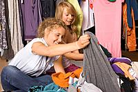 Two teenage girls looking through clothes
