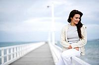 Woman Sitting on a Jetty Railing