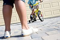 Mother Watching Son Ride Bike in Driveway