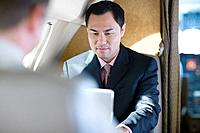 Businessman Using Laptop on Plane