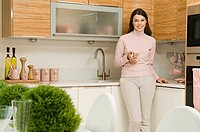 Woman in kitchen with coffee