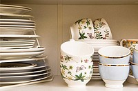 Teacups and plates in a cupboard