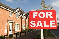 For sale sign and houses