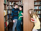 Girl spying on young couple in library