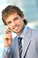 Young businessman using mobile phone, portrait