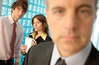 Businessman in office with colleagues in background (thumbnail)